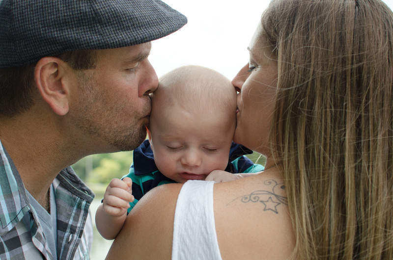 Parents kissing their 6 week old