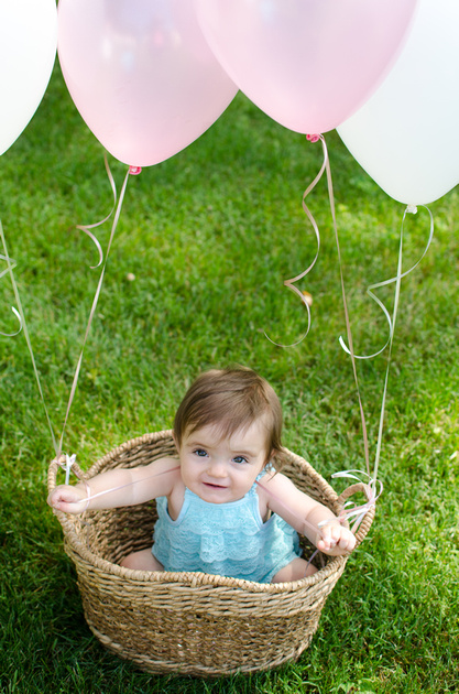 One Year old baby girl sitting in a basket with balloons.
