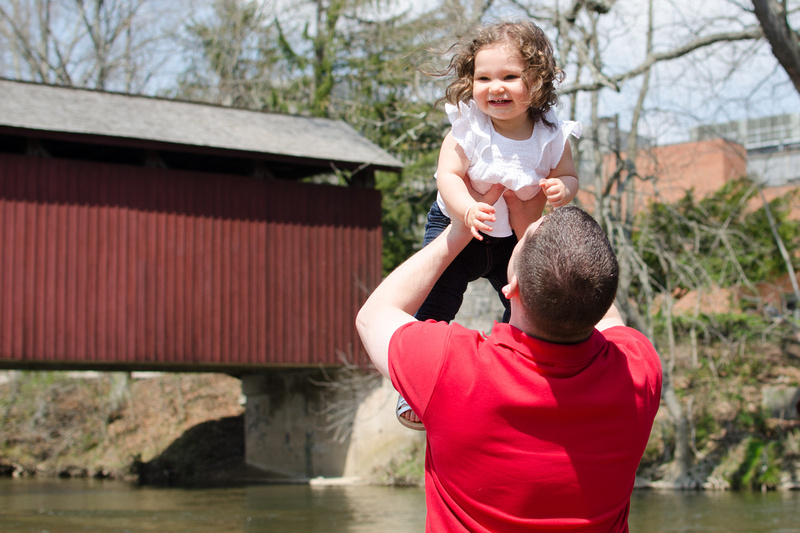 Father holding laughing daughter in the air.
