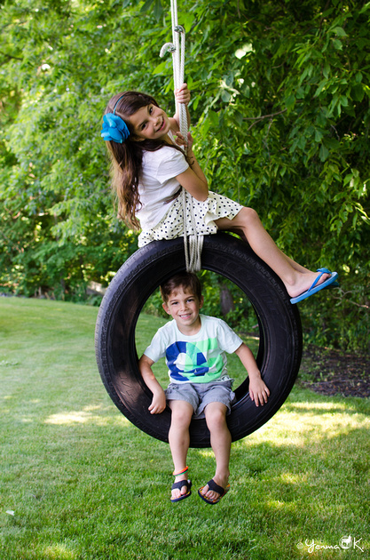 Two kids swinging on a tire swing in an outdoor portrait