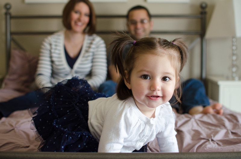 Adorable pigtailed girl in a blue tutu stealing the limelight in the family portrait.