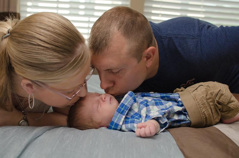 Parents kissing their newborn