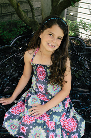 Outdoor portrait of a 7 year old girl sitting on a bench