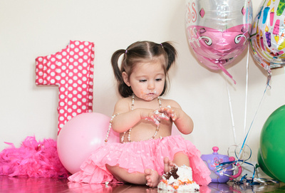 Celebrating turning one with a cupcake, balloons, and a pink tutu.