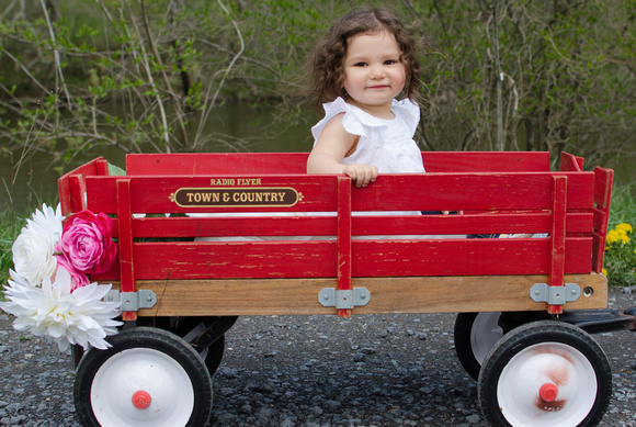 Portrait of a One year old, Ellie, in her red wagon.