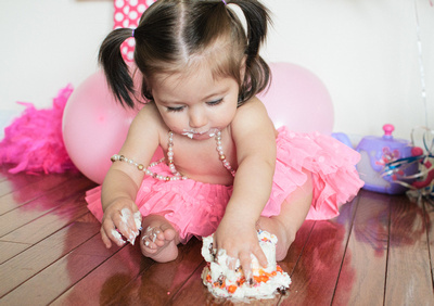 Pigtailed girl celebrates turning one by smashing a cupcake with her small hands.