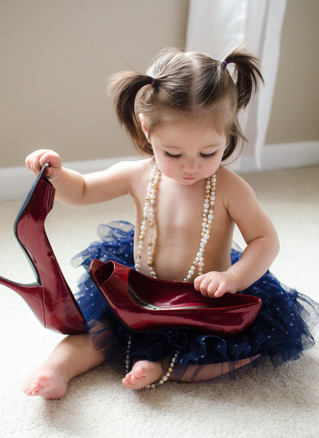Pigtailed girl celebrating turning one wearing mommy's heels and blue sparkly tutu.