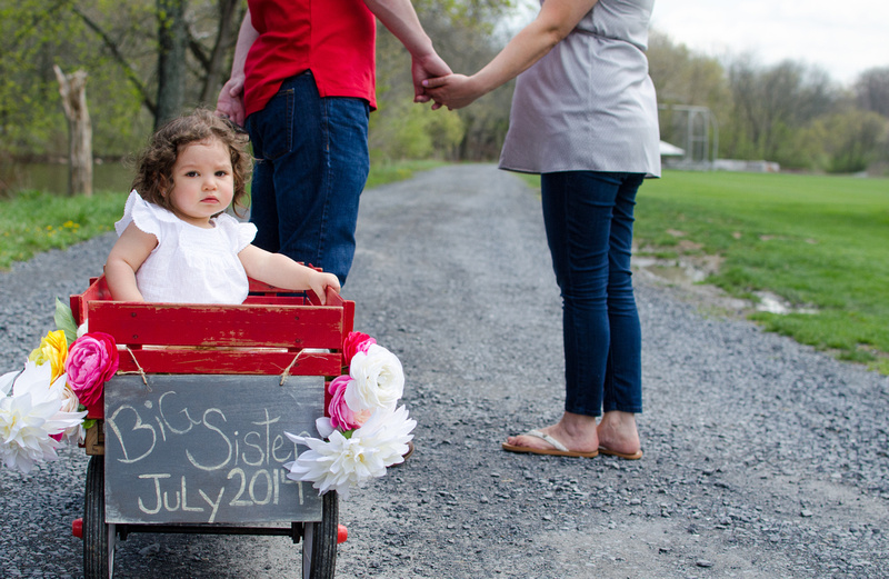 Mom and Dad are pulling a little red wagon with their daughter.