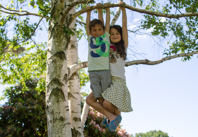 Outdoor Portrait of 2 Children Hanging from a Tree