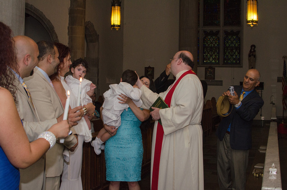 A toddler is Baptized by the Reverend.
