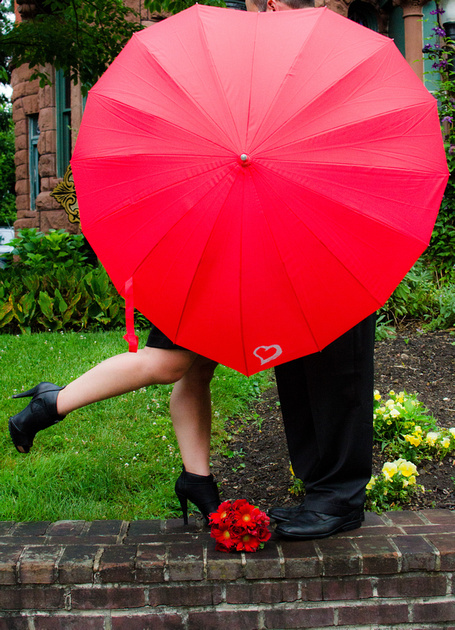 Newlyweds standing in front of their Wedding Reception Venue with a Red Umbrella