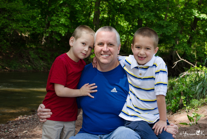 A portrait of a father with his 6 year old and 4 year old son at a creek.