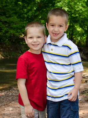 A 4 year old hugging his 6 year old brother in a portrait