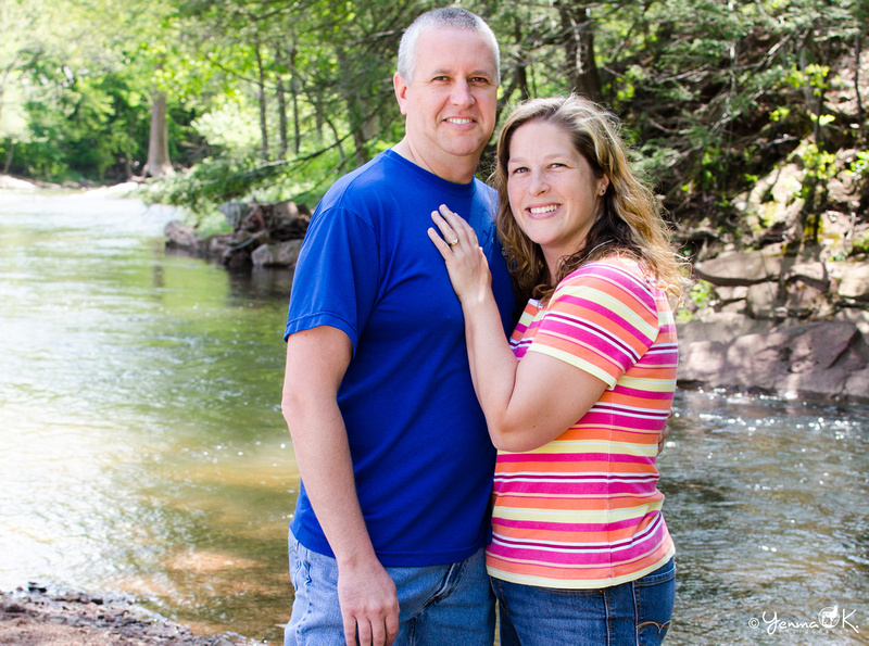 A portrait of a married couple standing by a creek.