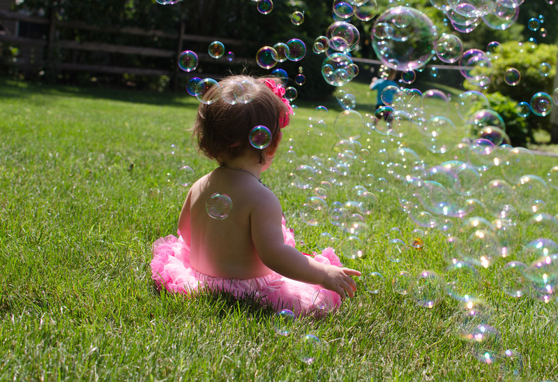 One year old baby girl in a cloud of bubbles